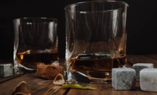 Due bicchieri di whisky vicino a qualche whisky stone